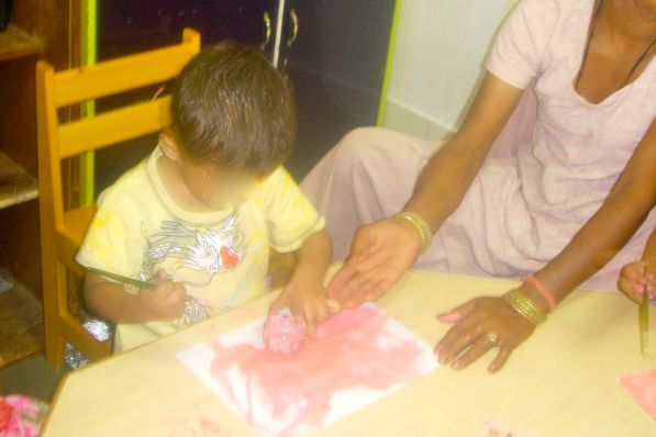 Raju pours the paint on the paper